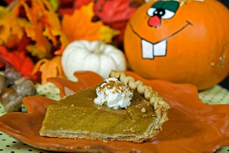 Slice of pumpkin pie with funny face pumpkin. photo