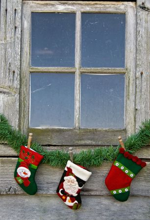 christmas sock: Holiday stockings hanging under old window. Stock Photo