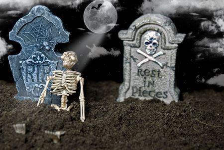 Skeleton leaning against a tombstone in dirt.