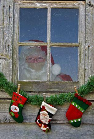 Santa peeking through an old house window. photo