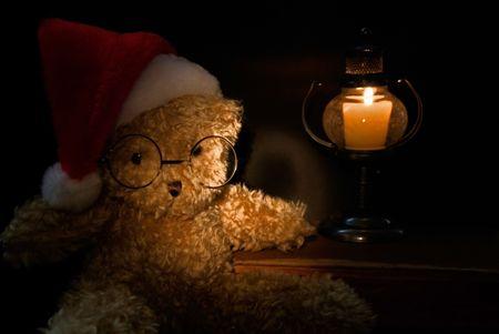 Christmas teddy bear illuminated by candlelight.