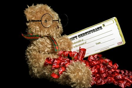 Teddy bear giving a holiday gift certificate.