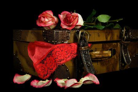 Rode kant lingerie en rozen met oude koffer.  Stockfoto