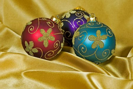 luster: Holiday ornaments on gold satin.