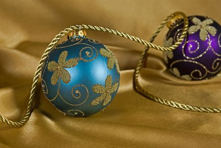 luster: Fancy holiday ornaments on gold satin.