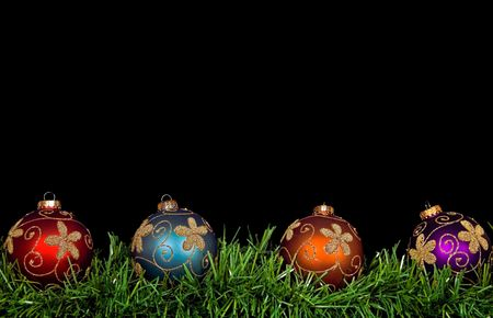Christmas ornaments in garland border on black.