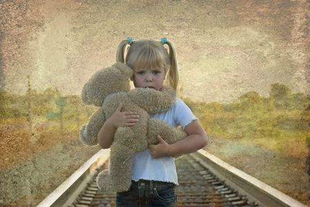 Little girl hugging her teddy bear on the railroad tracks. photo