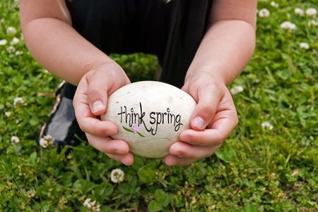 spring message: Spring message on goose egg held by child.