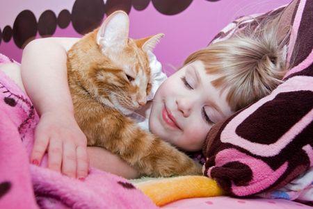 Little girl hugging her pet tabby cat.