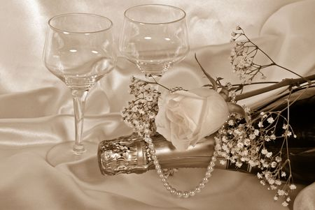 Rose and pearls on wine bottle with stemware in sepia. photo
