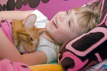 Cat licking a little girls arm. photo