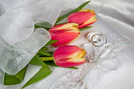Bridal tulip bouquet with rings on wedding pillow. photo