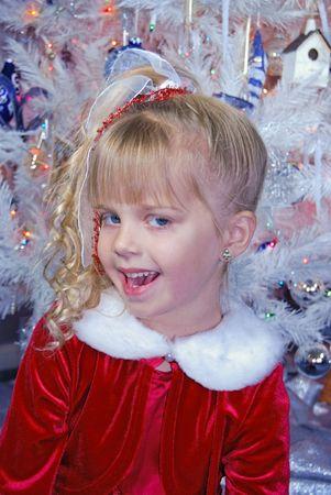 velvet dress: Smiling blond girl by Christmas tree.