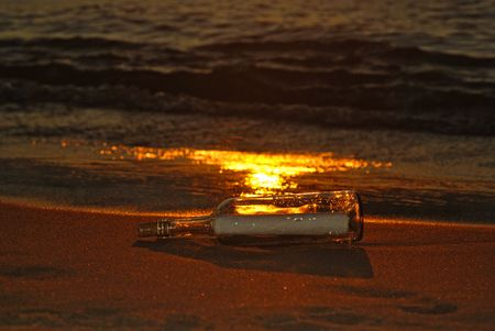 Message in bottle on a sunset beach. Stock Photo - 6624785