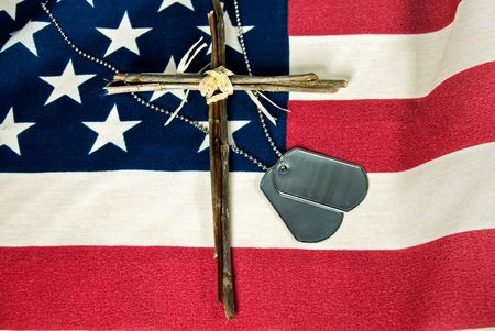 Military dog tags and cross on American flag. Imagens