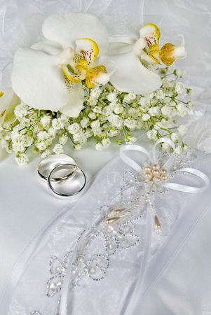 Orchid bouquet and silver rings on wedding pillow. Stock Photo - 6731377