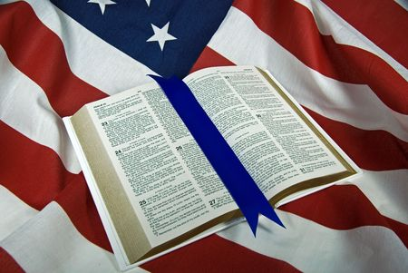 Open Holy Bible on American flag. Stock Photo
