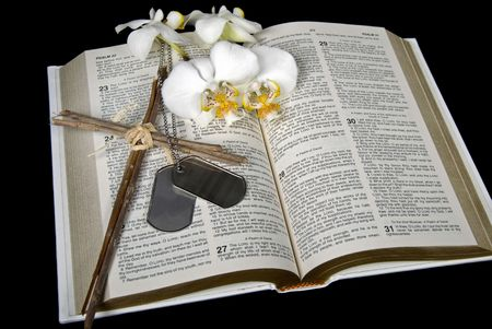 Military dog tags with homemade cross and orchid on Bible. photo