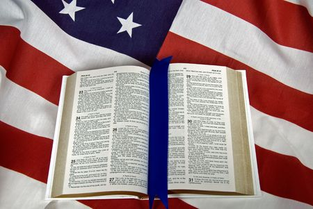 Open Holy Bible on an American flag. Stock Photo