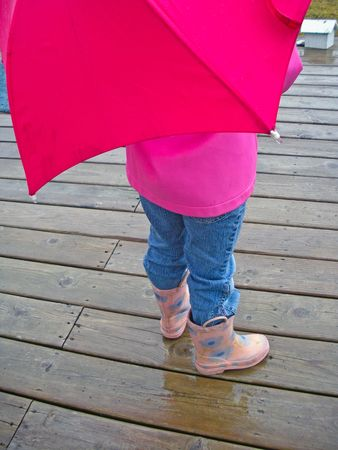 Child with umbrella, raincoat and boots in the rain. photo
