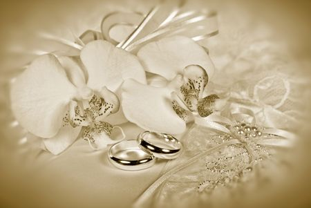 Orchid bridal bouquet with rings in sepia tones.