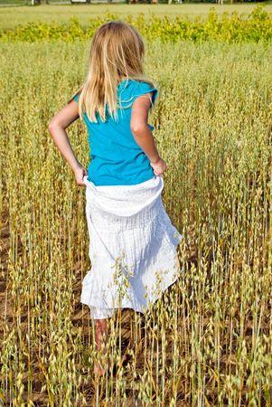 Young girl walking in wheat field.
