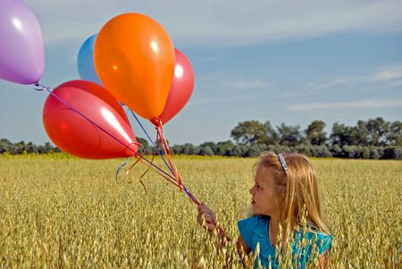 Little girl with balloon bouquet in field. photo