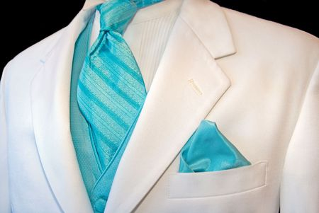 Bright turquoise accessories accenting a white tuxedo.