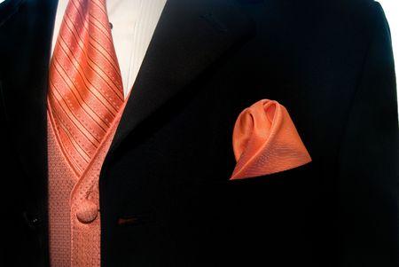 Peach colored accessories accenting a black tuxedo. photo