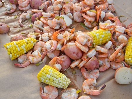 Mix of shrimp, corn on the cob and red potatoes on brown paper. Stock Photo