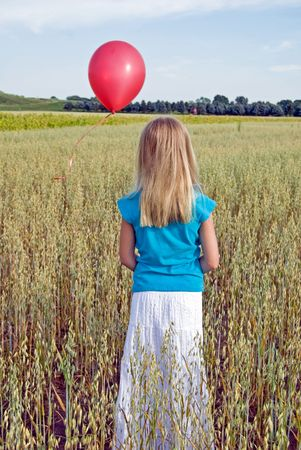 Young girl in field releasing a red balloon.
