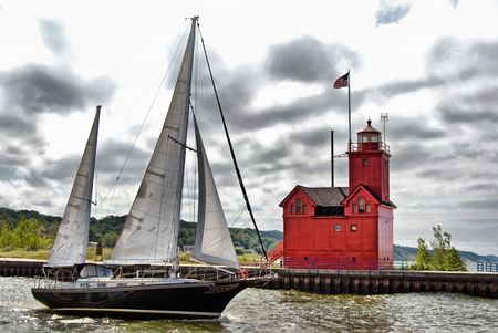 Old sailboat and red lighthouse in HDR.