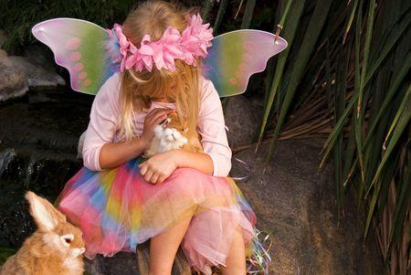 Little fairy girl petting a bunny in garden.