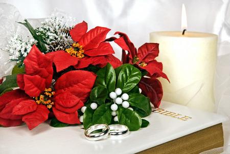 Kerstmis boeket en ringen op de Heilige Bijbel.