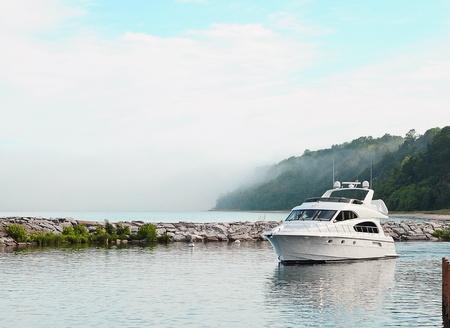 sleek: Sleek white yacht anchored in cove.