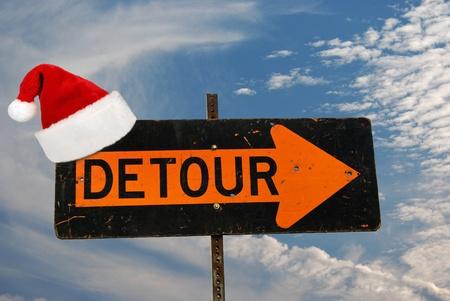 detour: Santa hat hanging from a detour sign.