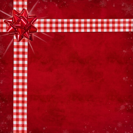 Red bow on gingham ribbon with red textured background. photo