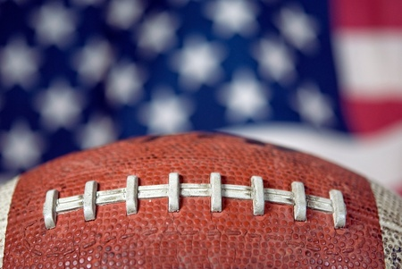 pigskin: Extreme close up of a football with flag background. Stock Photo