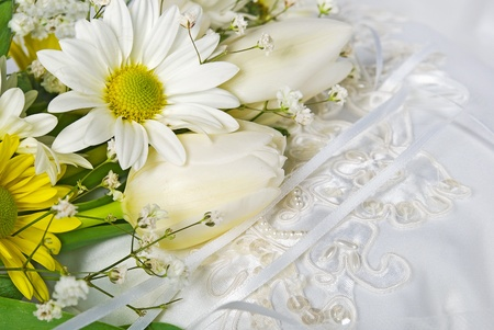 Daisy and tulip wedding bouquet on satin pillow. photo