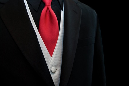 Red tie accenting a black tuxedo.