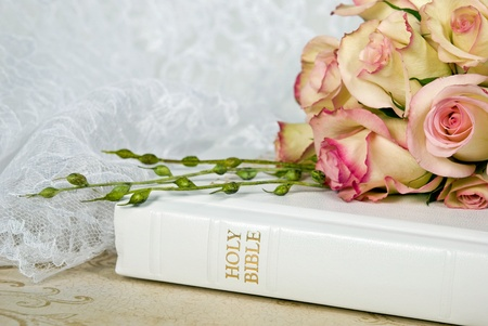 Bridal rose bouquet on white bible.