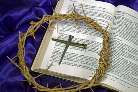 rusty nail: Crown of thorns and spikes on Holy Bible. Stock Photo