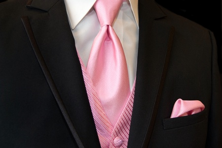 Pink tie and vest accenting a black tuxedo.