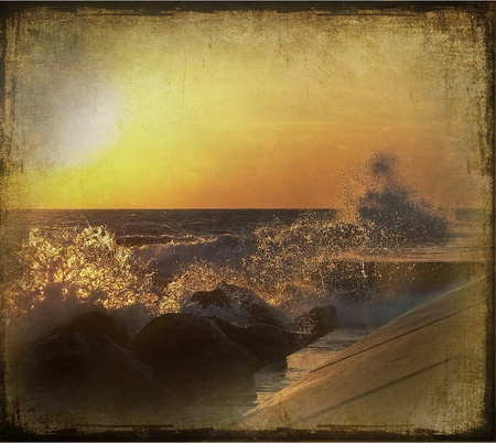 Vintage vignetting and texture on sunset waves crashing on pier.