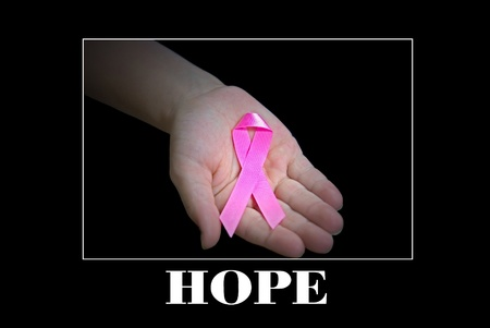 Breast cancer awarenes ribbon in little girls hand.
