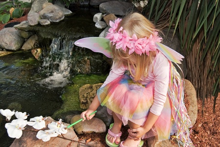 Fairy child painting a white orchid by waterfall. Stock Photo
