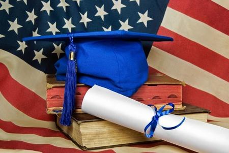 ブルーの卒業キャップと古い書物の卒業証書。
