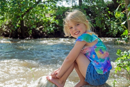 Little girl on a rock by rushing river. Stock Photo - 9536579