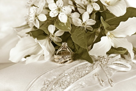 wedding rings with bridal bouquet on pillow