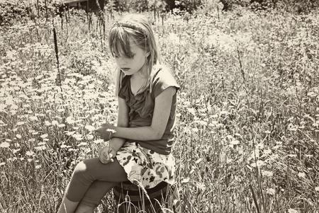 fille triste: jeune fille sur le baril en bois champ daisy sauvages